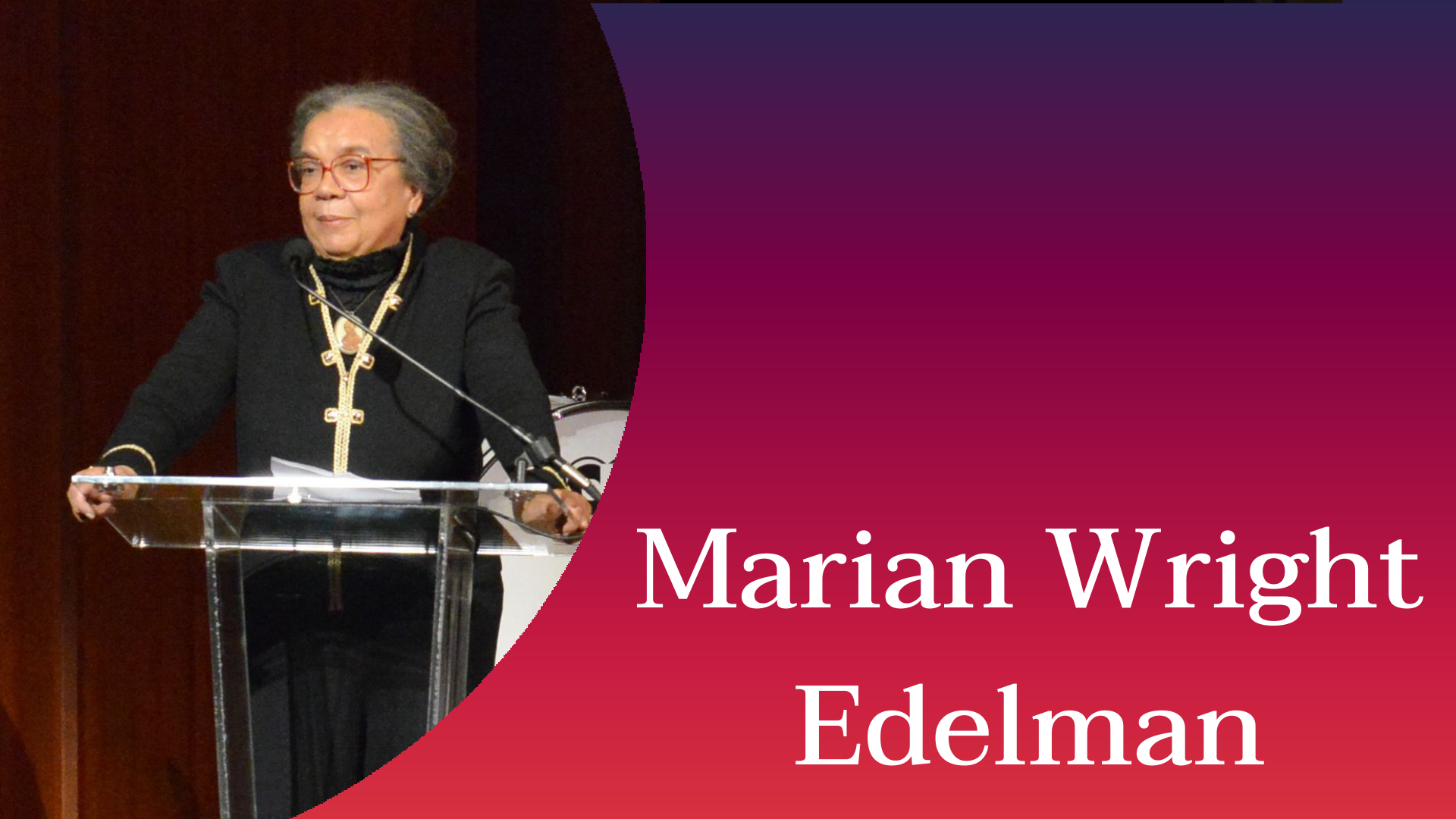 Marian Wright Edelman on stage with a drum set behind her. She is dressed in a black suit with a yellow collar and wearing a medal on her neck. There is a microphone stand in front of her and her mouth is above the microphone. Next to her is a curve of an orange, pink, and purple color palette with her name written in white.
